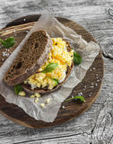 Scramble egg sandwich on rustic wooden background. Healthy breakfast or snack Stock Image