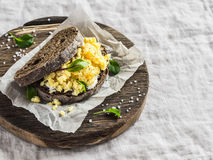 Scramble egg sandwich on rustic wooden background. Healthy breakfast or snack Stock Photo
