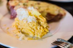Scramble egg served with sliced baguette topping with bacon and cheese at the restaurant in Chiang Mai, Thailand.  Stock Images