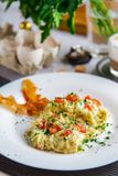 Scramble of eggs and bacon on a white plate close-up royalty free stock photography