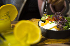Scramble eggs in black iron plate with vegetables. In the restaurant. Orange juice with slice of citrus t Stock Images