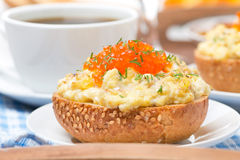 Scramble eggs with red caviar and greens on a wheat bun, closeup Royalty Free Stock Images