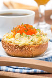 Scramble eggs with red caviar on wheat bun Royalty Free Stock Image