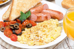Scramble eggs with tomatoes, grilled sausages and toast. For breakfast, close-up, top view stock images