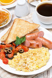 Scramble eggs with tomatoes, grilled sausages and toast. Vertical Royalty Free Stock Images