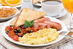 Scramble eggs with tomatoes, sausage and toast for breakfast Stock Photos