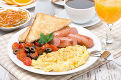 Scramble eggs with tomatoes, sausage and toast on a plate Royalty Free Stock Images