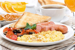 Scramble eggs, tomatoes, sausages and toast Royalty Free Stock Images