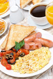 Scramble eggs with tomatoes, sausages and toast Royalty Free Stock Photos