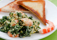 Scrambled. Eggs with spinach and prawns Royalty Free Stock Photo