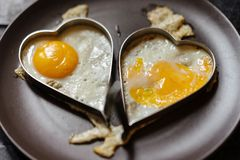 Scrambled couple eggs in hearts. Love theme. royalty free stock photos