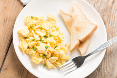 Scrambled egg and bread on white plate. Top view. Royalty Free Stock Images