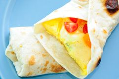 Scrambled egg breakfast burrito with tomatoes and green onion an Royalty Free Stock Photos