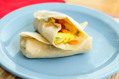 Scrambled egg breakfast burrito with tomatoes and green onion an Stock Image