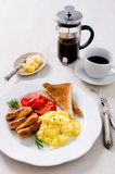 Scrambled egg breakfast with sausages, tomatoes and coffee Royalty Free Stock Photos