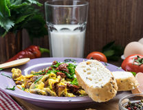 Scrambled egg with dried tomatoes and home baked goods Royalty Free Stock Photos
