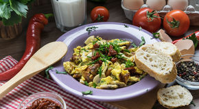 Scrambled egg with dried tomatoes and home baked goods Royalty Free Stock Photo