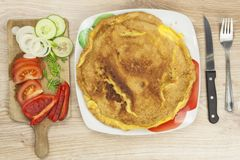 Scrambled egg omelet with vegetables on a wooden table. Royalty Free Stock Photos