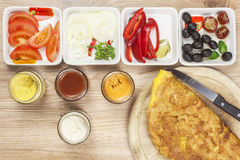 Scrambled egg omelet with vegetables on a wooden table. Royalty Free Stock Photography