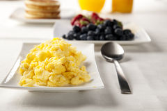 Scrambled Eggs. On the breakfast table with a serving spoon Royalty Free Stock Photo