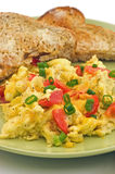 Scrambled eggs. With red pepper, green onion and cheddar cheese, with warm buttered whole wheat toast Royalty Free Stock Photos