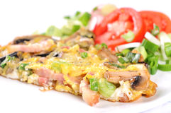 Scrambled eggs. With mushrooms and ham and green onions, tomatoes on white Stock Images