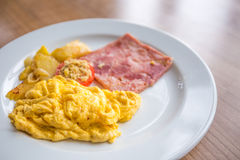 Scrambled eggs as breakfast. Breakfast with scrambled eggs, slice pork ham, tomato, and potato Stock Image