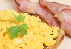 Scrambled Eggs with Bacon. Scrambled eggs with toast and grilled back bacon Stock Image