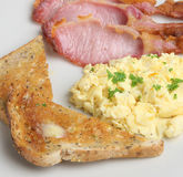 Scrambled Eggs and Bacon. Scrambled eggs with back bacon and buttered wholemeal toast Stock Photos