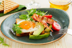 Scrambled eggs with bacon. And avocado Stock Photo