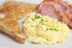 Scrambled Eggs and Bacon Breakfast. Scrambled eggs with bacon and wholemeal toast Royalty Free Stock Image