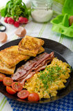 Scrambled eggs with bacon and French toast Stock Images