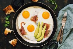 Scrambled eggs with bacon in a frying pan, avocado, toast. Breakfast on a dark background, top view. royalty free stock photo