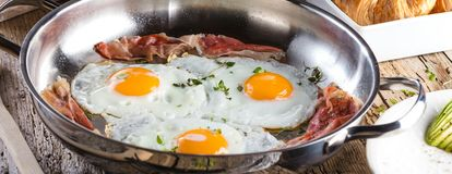 Scrambled eggs and bacon on frying pan on table close-up stock photos