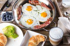 Scrambled eggs and bacon on frying pan on table close-up stock images