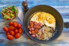 Scrambled eggs with bacon, onion and sausage stock photo