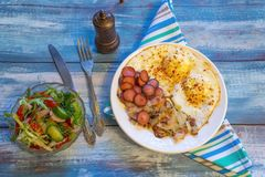 Scrambled eggs with bacon, onion and sausage royalty free stock images