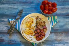 Scrambled eggs with bacon, onion and sausage stock photos