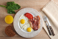 Scrambled eggs with bacon, spinach and beans on the plate Stock Image