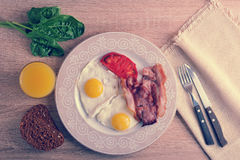 Scrambled eggs with bacon, spinach and beans on the plate Stock Photo