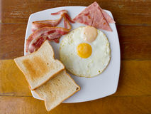 Scrambled eggs with bacon and  toast. On white plate on the table Stock Images