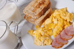 Scrambled eggs with bacon, toast and milk. For breakfast Stock Photos