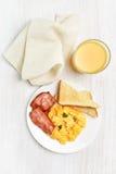 Scrambled eggs, bacon, toasts Stock Photos