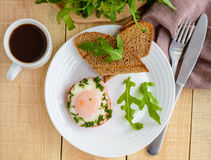 Scrambled eggs, baked in a ring bell pepper, toast, arugula leaves and a cup of coffee. Stock Photos