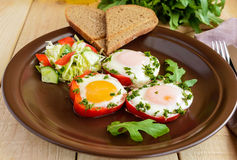 Scrambled eggs baked in a ring bell pepper, toast, arugula leaves and a light salad with cabbage, bell pepper, cucumber. Stock Photo