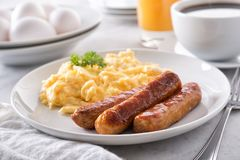 Scrambled Eggs and Breakfast Sausage. A plate of delicious scrambled eggs and breakfast sausage with coffee and orange juice royalty free stock images