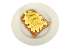 Scrambled Eggs Breakfast on Wholemeal Toast with Avocado on a plate isolated white background Royalty Free Stock Photography