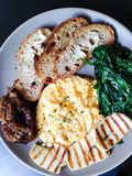 Scrambled eggs brunch. With halloumi cheese, toast with butter, spinach and caramelized onions Royalty Free Stock Photography