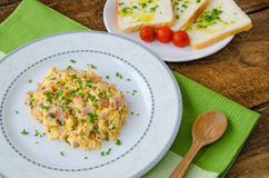 Scrambled eggs with chive and bacon, toast with herbs Royalty Free Stock Image