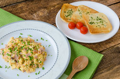 Scrambled eggs with chive and bacon, toast with herbs Stock Images